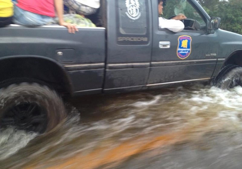 Pick up truck driving on a flooded road in Thailand
