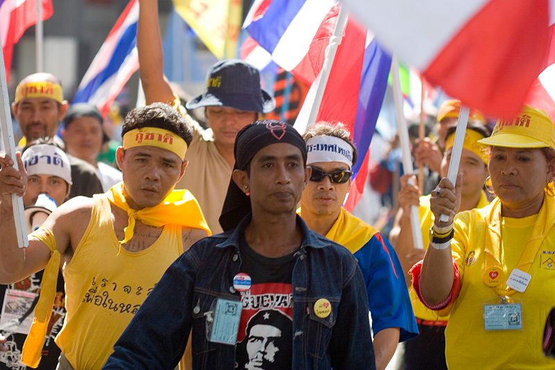 PAD Anti-Thaksin protesters walk on Bangkok street wearing yellow t-shirts
