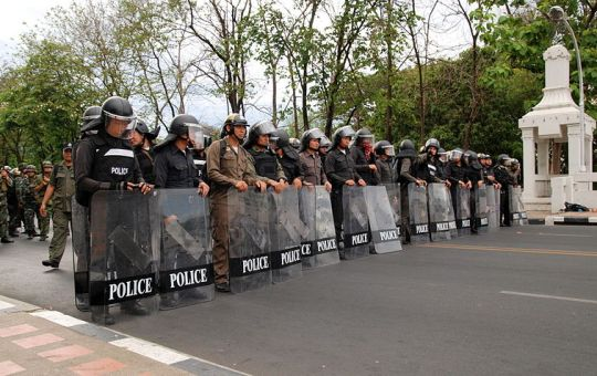 A line of policemen and policewomen equipped with riot shields at Naorawat bridge in Chiang Mai