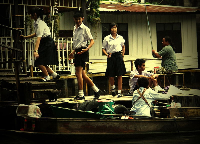 Thai schoolgirls coming back from school by boat