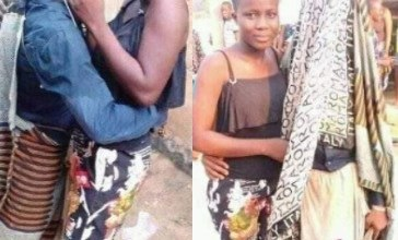 Man dressed in ''Egungun'' attire stops his performance to kiss his woman