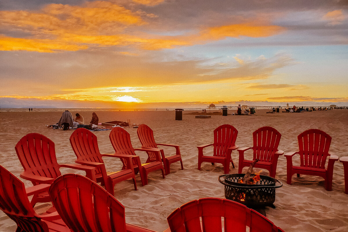 Red chairs around a bonfire pit on Huntington City Beach at sunset.