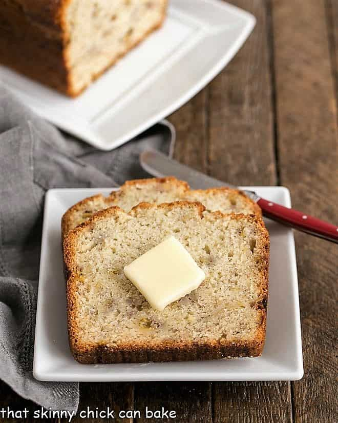 2 slices of Buttermilk Banana Bread on a square white plate topped with a pat of butter