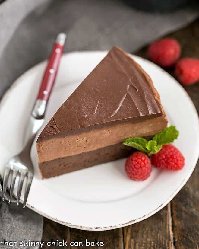 Frozen Chocolate Mousse Cake on a white plate with raspberry garnish