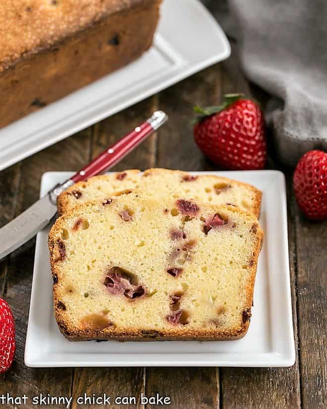 Fresh Strawberry Pound Cake slices on a square white ceramic plate with a red handled knife