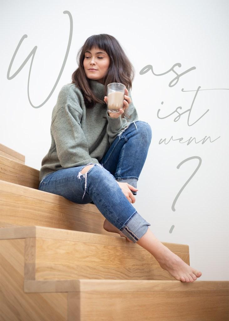 Frau sitzt mit Kaffeetasse auf einer Holztreppe