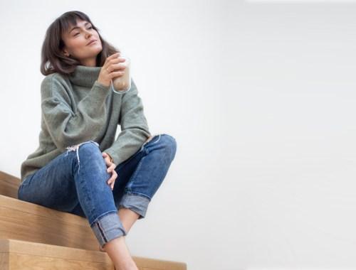 Frau sitzt mit Kaffeetasse auf der Treppe