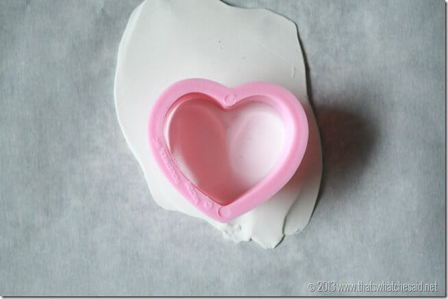 Showing how to line up heart cookie cutter to grab both thumbprints to make the charm