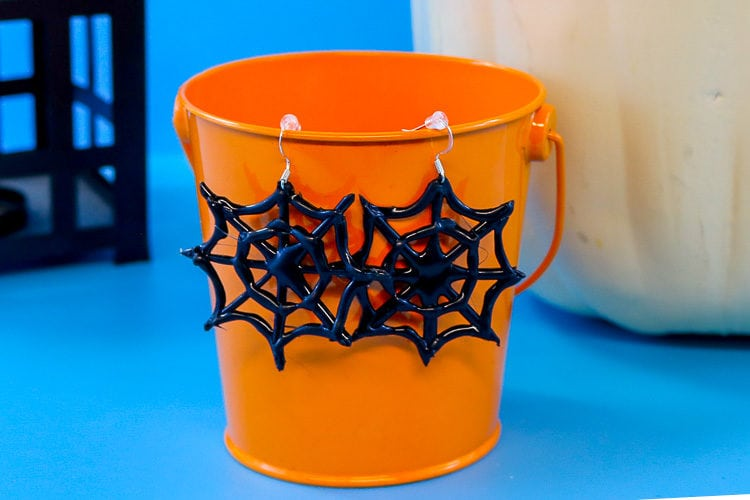 Completed hot glue spider web earrings hanging on a small orange bucket