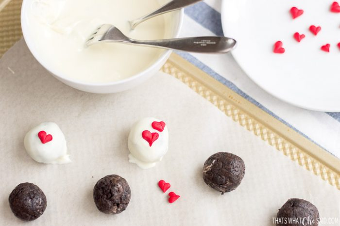 Adding fondant hearts to the tops of chocolate dipped oreo truffles