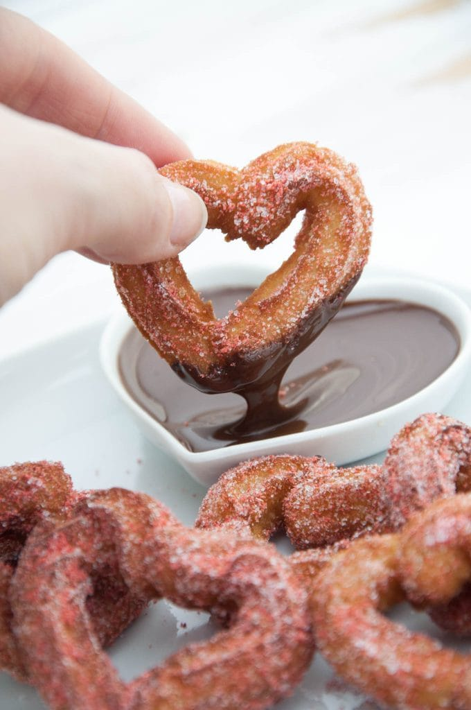heart shaped churro being dipped in chocolate sauce