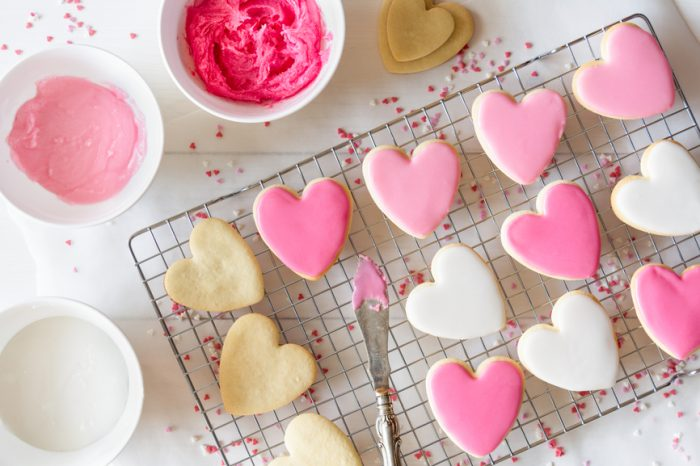 Heart cookies on a cooling rack with different shades of pink and white royal icing