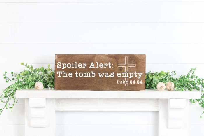 White mantel with greenery and flowers and a wooden sign. Easter religious svg in white on the sign