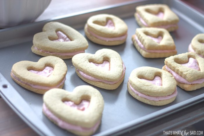 Baking sheet with shortbread cookies sandwiching raspberry filling