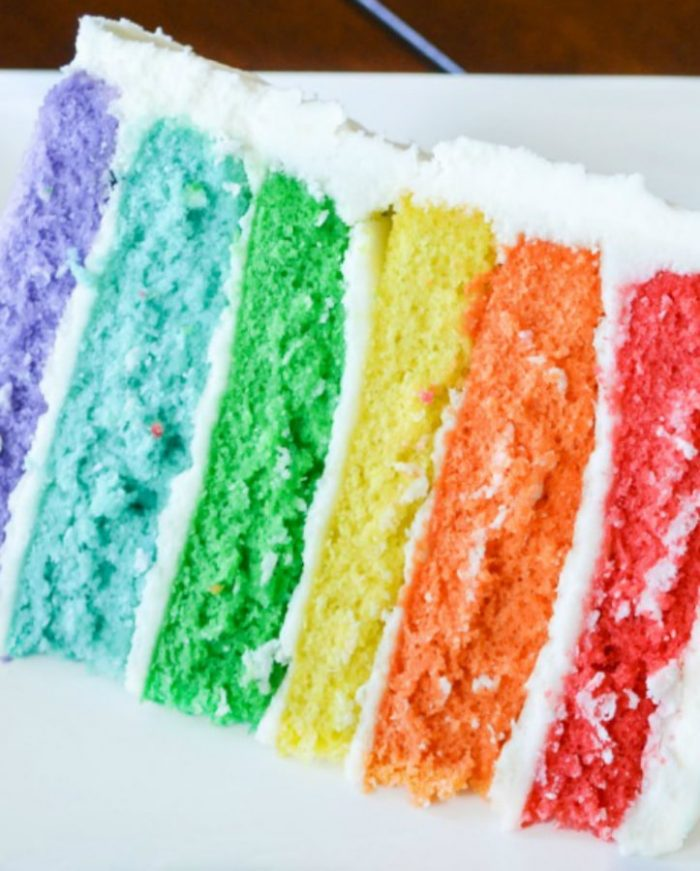 Cake in rainbow layers with white buttercream icing in between the layers and outside the cake
