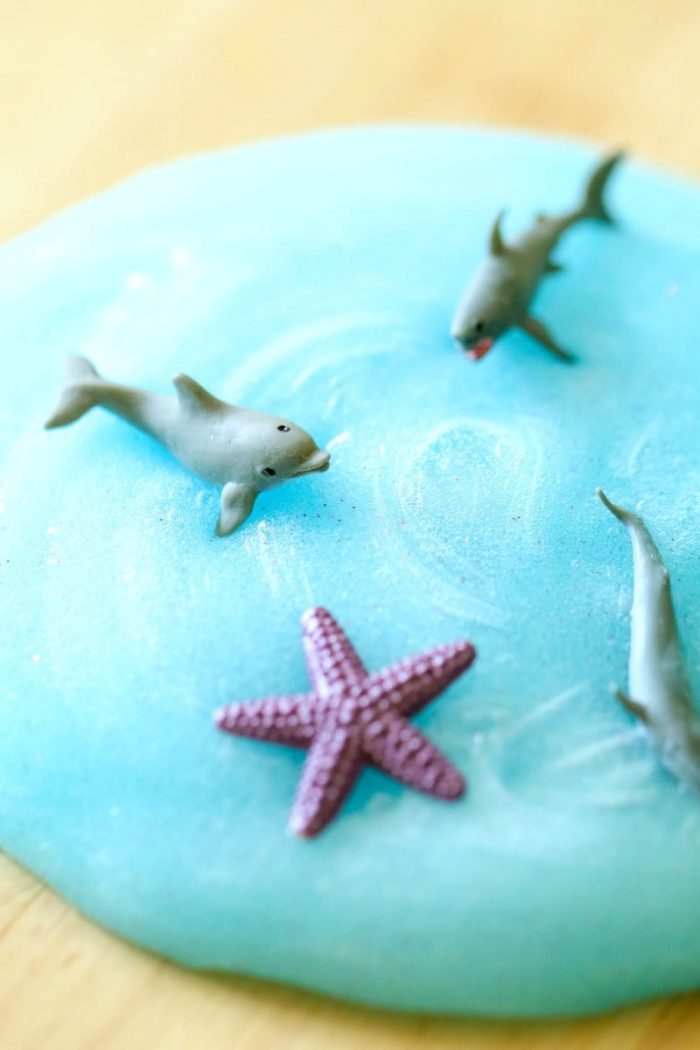 Blue sparkly slime with plastic ocean creatures swimming in it.