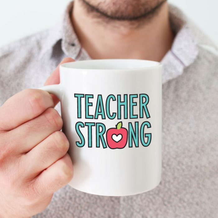 """Man holding white coffee mug with """"Teacher Strong"""" design in adhesive vinyl - square format"""
