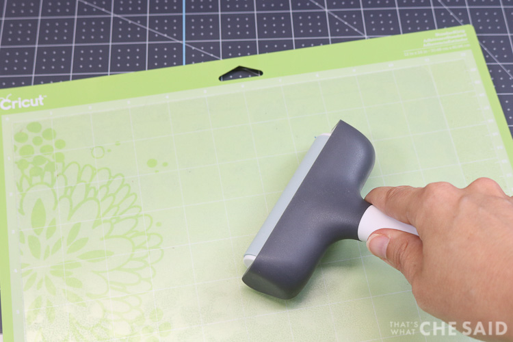 Using the Brayer to firmly adhere the plastic cutting mat from dollar sore onto to a 12x24 Standard Grip (green) mat