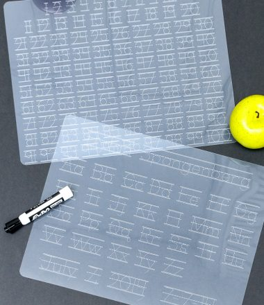 """Dollar store plastic cutting mats turned Alpha and Numeric tracing mats using a Cricut Machine - Vertical shot both mats on black """"chalkboard"""" background"""