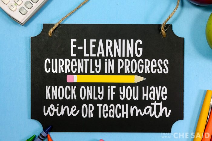 Black Chalkboard Rectangular Sign with E-Learning SVG applied in vinyl and school related items around, calculator, apples, crayons
