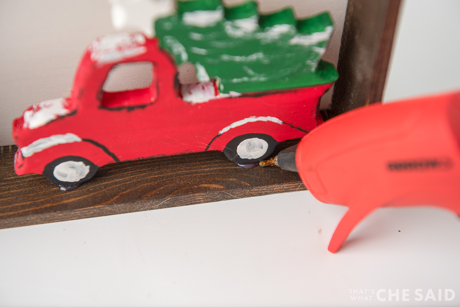 Hot gluing truck ornament into sign