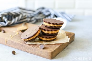 Finished peanut butter cups on small wooden board with towel in background
