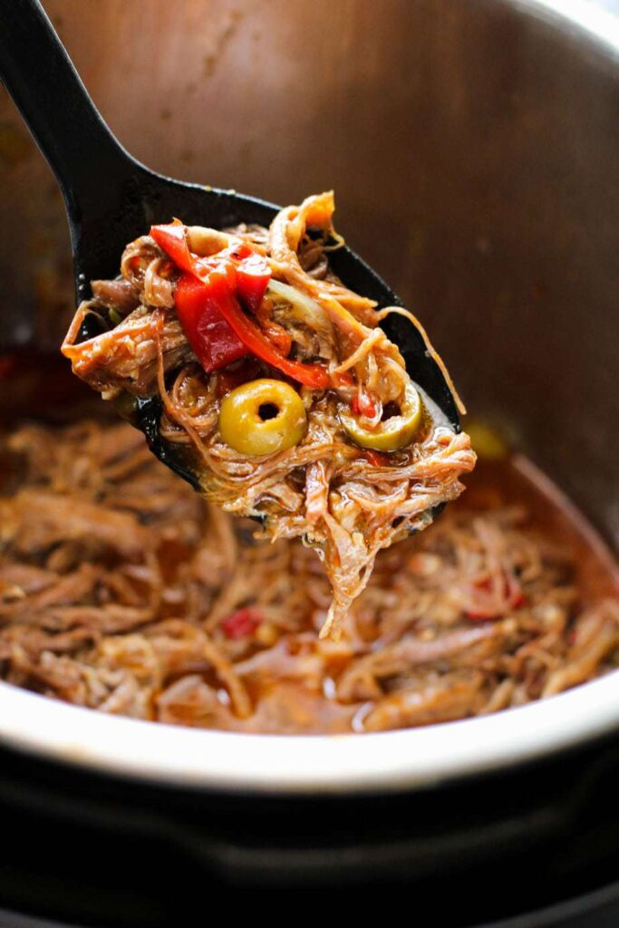 Serving spoon full of Cuban Ropa Vieja over the inner pot of the instant pot