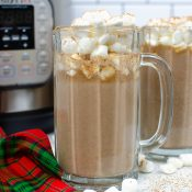 Horizontal view of Tuxedo Hot Chocolate in a tall glass mug with marshmallows on top. Another mug and Instant pot is in the background