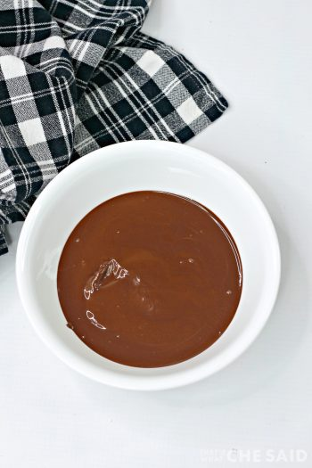 White bowl with melted chocolate wafers with black plaid fabric napkin
