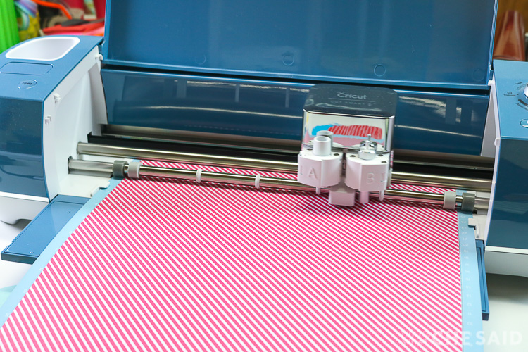 Denim colored Cricut Explore Air 2 cutting cardstock of white and pink diagonal lines