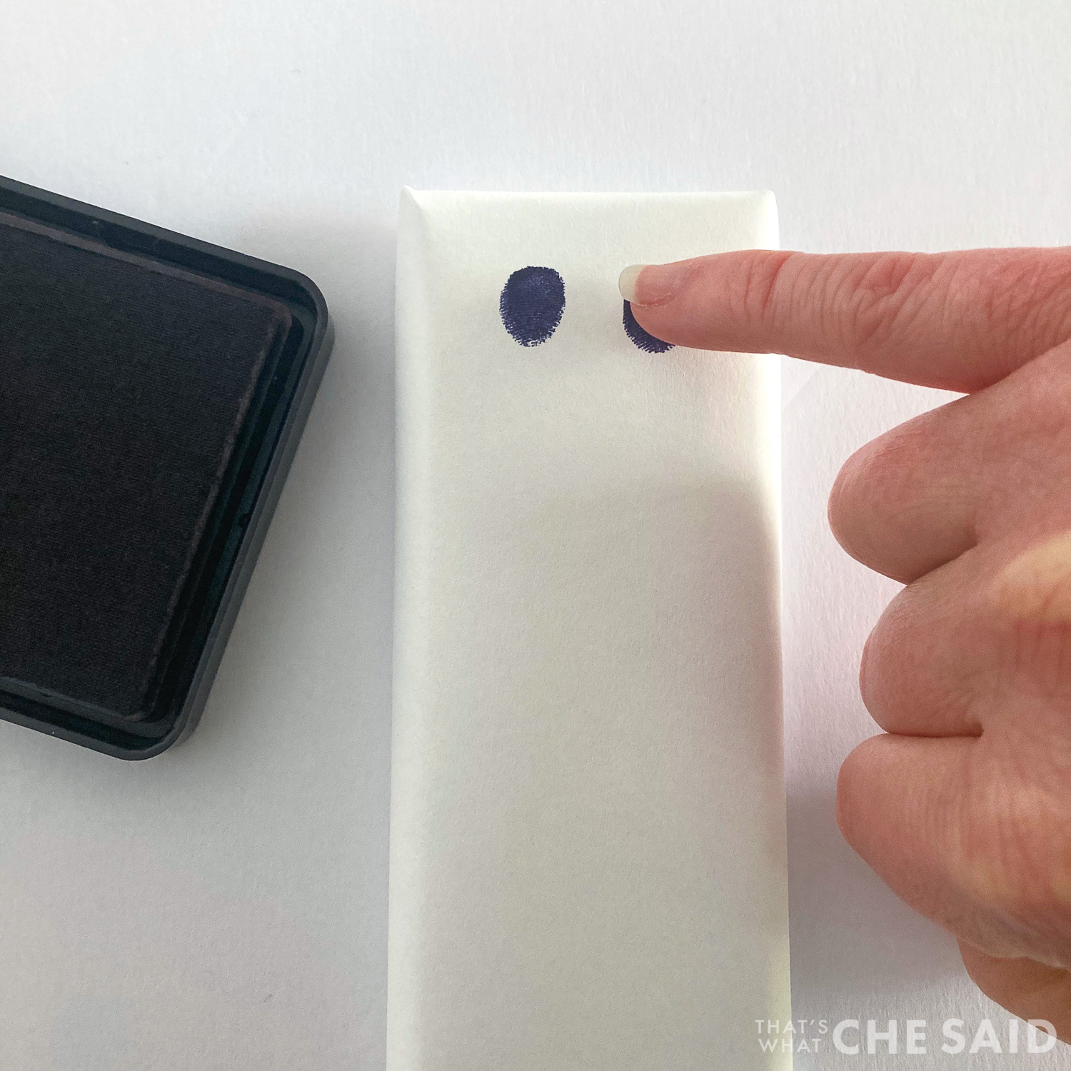 Adding eyes with black stamp pad and pinky fingerprint