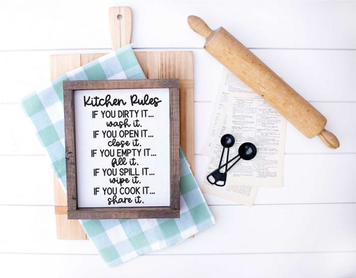 White wood with Cutting Board, kitchen towel, meansuring spoons, rolling pin and sign that has kitchen rules svg applied in horizontal format