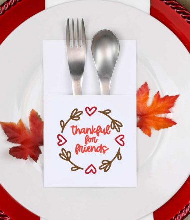 Fall place setting with paper silverware holder with friendsgiving svg design on it vertical orientation