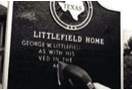 A person sands the letters on a historical marker to remove black lacquer in the process of restoration