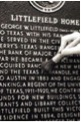 A hand uses a small brush to brush off letters on a historical marker in the process of restoration