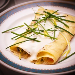Rolled crepes with a white sauce and chives for garnish.