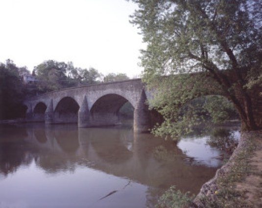 Wilson Bridge, the oldest and perhaps the most graceful of Washington County's limestone arches, was considered a modern marvel at the time of its completion in 1819. Its fine workmanship, by the mason Silas Harry, served as a pattern for some thirty stone bridges that would follow in the region. The five-arch, 210-foot-long bridge carried the state-chartered National Pike (later designated US 40) over Conococheague Creek to join the National Road at Cumberland, providing a pivotal link between eastern seaport cities and western markets. Wilson Bridge was bypassed in 1936, when US 40 was rerouted and a newer bridge built downstream. It remained open for local traffic until 1972, when flood damage from Tropical Storm Agnes relegated it to foot traffic.