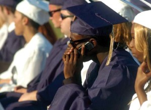 Alishawaine Raheen Everette Monk takes a moment to talk on his cell phone Friday during commencement ceremonies at Perryville High School.  Cecil Whig photo by Matt Given
