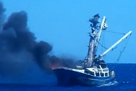 This image is of fishing vessel Betty C engulfed in smoke and flames 230 miles from Jarvis Island, Nov. 29, 2014. All 21 crewmembers aboard Betty C abandoned ship and were rescued because of an emergency position-indicating radio beacon. (U.S. Coast Guard courtesy photo by Francisco Javier Perez)