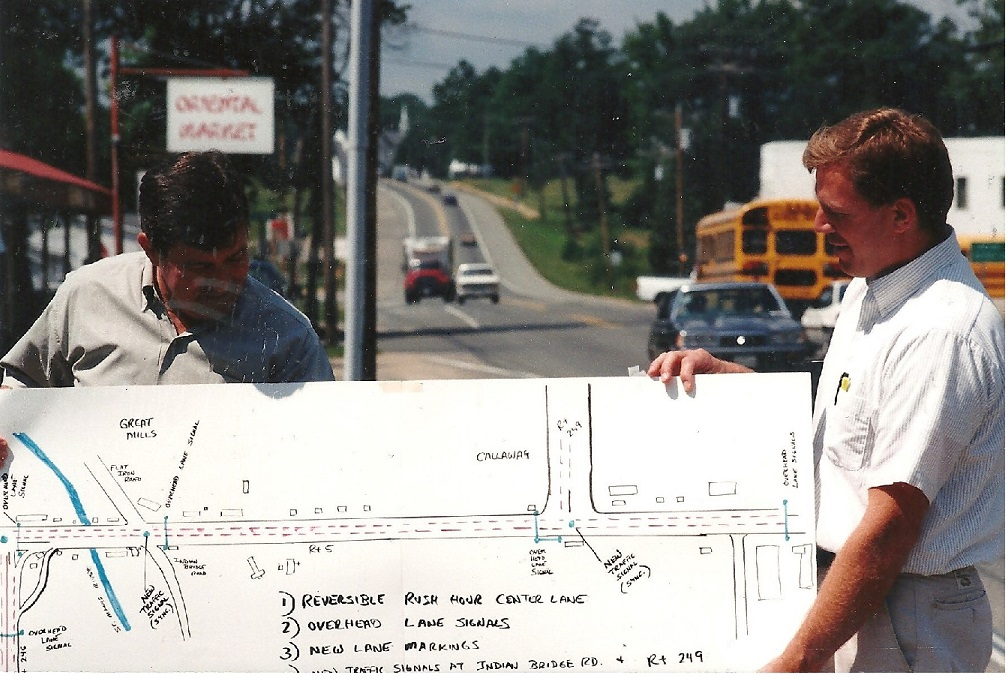Roy Dyson and John Bohanan shown hold a SHA plan to eliminate the bottleneck on Rt. 5 at Great Mills with reversible rush hour center lane that neither of them bothered to promote.