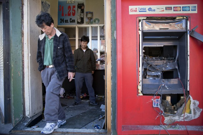 A Korean business owner in the doorway of his destroyed store. AP photo