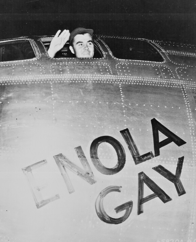 Col. Paul W. Tibbets, Jr., pilot of the ENOLA GAY, the plane that dropped the atomic bomb on Hiroshima, waves from his cockpit before the takeoff, 6 August 1945