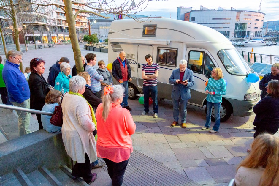 Bishop Harold reads to Chris and Susan and guests from the Bible alongside the camper van parked at the DOCK Cafe