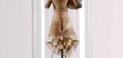Miniature mannequin with bird legs, dressed in vintage fabric, all under glass dome