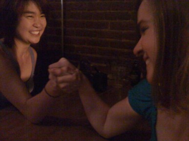two women arm wrestling and smiling