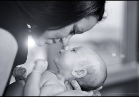 Mother touches noses with her new baby