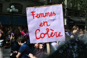 "Picture of a white protest sign with ""femmes en colère"" written in red cursive text"