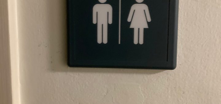 "Photo of the sign next to a single-user bathroom in the basement of the stake center in Oakland, California. It is labeled ""Rest Room"" and has a ""man"" image and a ""women"" image underneat."