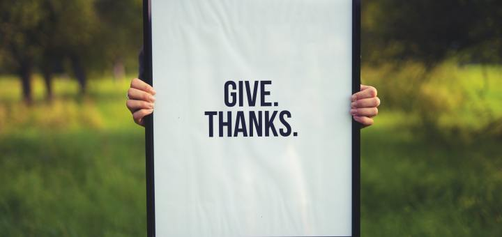 "a person holding a framed poster that says ""give thanks"""