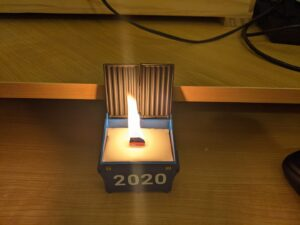 "Lit candle in a small metal model of a dumpster, with the text ""2020"" on the front"